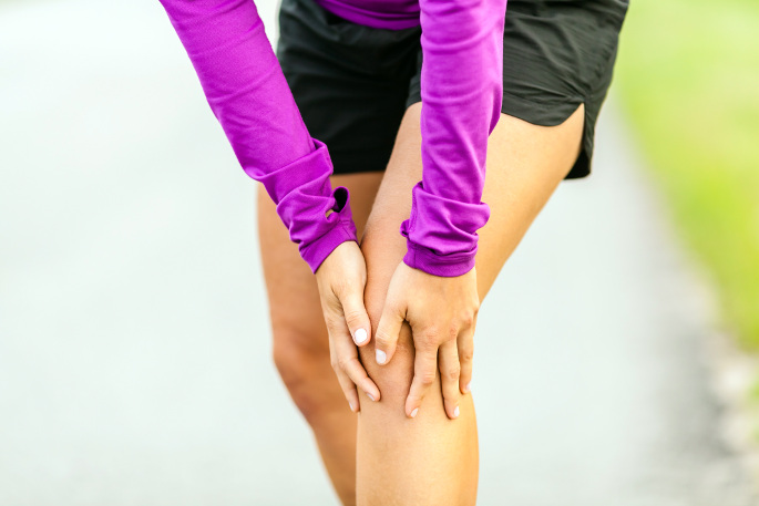 Doctor For Knee Pain - woman holding knee in pain