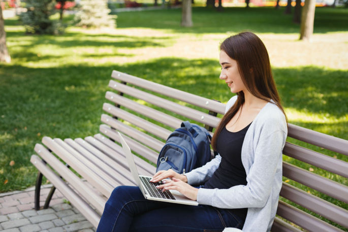 PRP Face Lift - woman on laptop sitting on bench